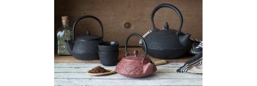 Ceainic din fonta pe suport de lemn langa o cupa cu ceai