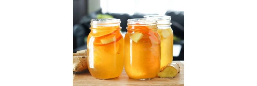 Trei borcane cu felii de portocale in ceai kombucha si ghimbir