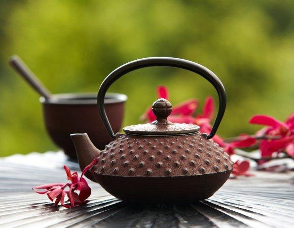 Ceainic si cupa de fonta pe o masa