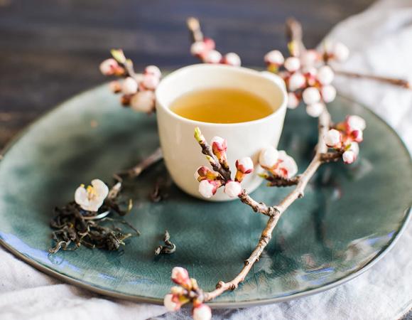 Ceasca cu ceai inconjurata de frunze de ceai